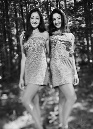 two persons only: Portrait of female twins standing together smiling
