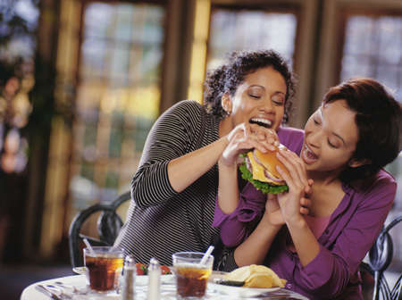 two persons only: Two young women fighting over a burger LANG_EVOIMAGES