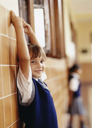 invariable: Young girl standing against a wall with her hands raised holding on to a ledge