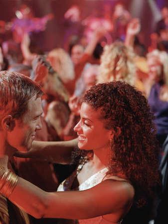 pareja bailando: Joven pareja bailando juntos en una discoteca