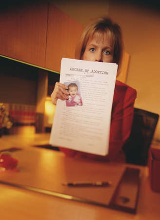 one sheet: Portrait of a mid adult woman holding a document LANG_EVOIMAGES