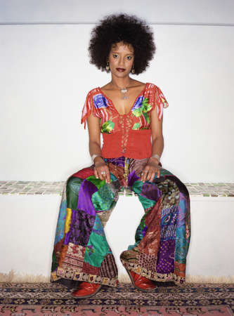 ethiopian ethnicity: Portrait of a woman in a colorful outfit sitting down