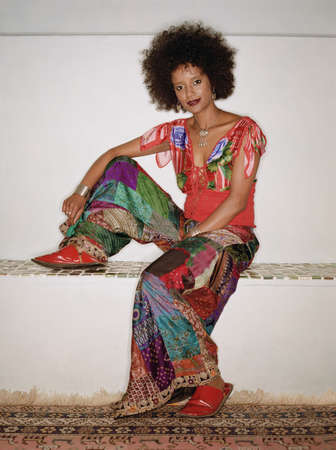 ethiopian ethnicity: Portrait of woman in colorful outfit sitting down with one leg up
