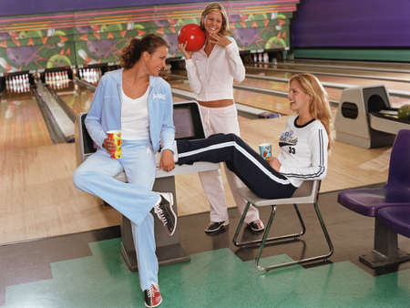 bowling alley: Three young women at a bowling alley LANG_EVOIMAGES
