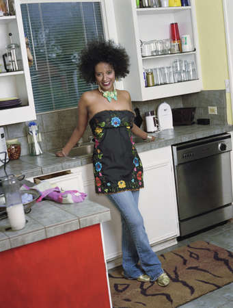 counteract: Portrait of a young woman standing in a kitchen