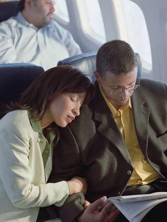 pareja durmiendo: Mujer que duerme en el hombro de un hombre en un plano aerodin�mico