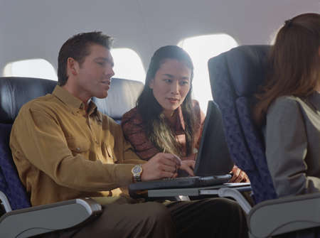 hydroplane: Business couple working on a laptop in an airplane