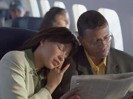 dormant: Mid adult woman sleeping on a mid adult mans shoulder in an aero plane