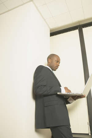 expressional: Businessman standing in a stairway operating a laptop LANG_EVOIMAGES