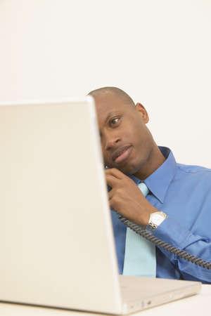 determines: Uomo d'affari a parlare su un telefono guardando un computer portatile