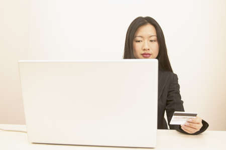 determines: Businesswoman sitting at a desk operating a laptop