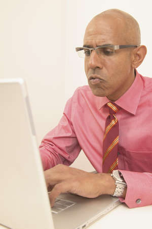 determines: Businessman seated at a desk operating a laptop