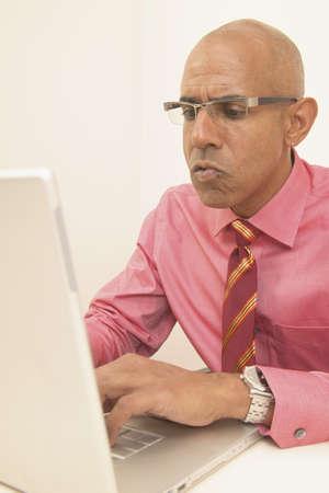 determines: Uomo d'affari seduto a una scrivania di funzionamento di un computer portatile
