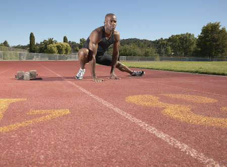 leeway: Young man stretching on a running track