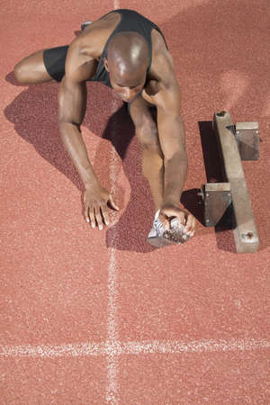 leeway: High angle view of a young man stretching on a running track LANG_EVOIMAGES