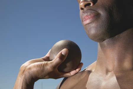 put away: Young man holding a shot put ball