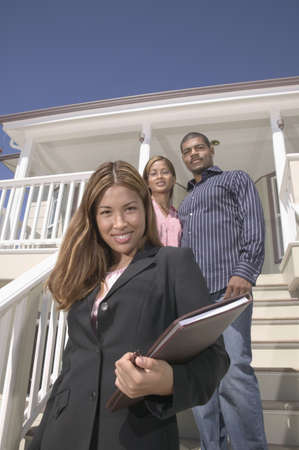 Young woman and a young couple standing on stairs to a house Stock Photo - 16045480