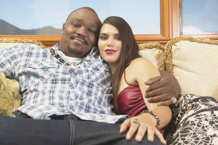 effrontery: Young couple sitting on a couch looking at camera smiling