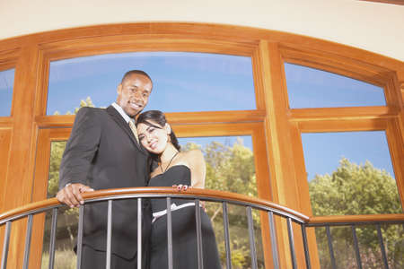 Young couple standing on a balcony looking down Stock Photo - 16045497