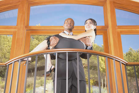 anecdote: Young man carrying a young woman on a balcony