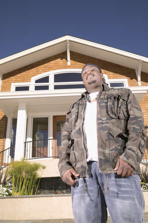 hauteur: Low angle view of a man standing in front of a house