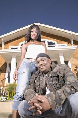 anecdote: Low angle view of a man squatting in front of a house with a young woman standing behind