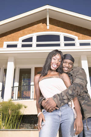 hauteur: Man holding a young woman in front of a house LANG_EVOIMAGES