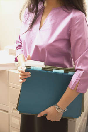 Young businesswoman standing in an office holding files Stock Photo - 16045512