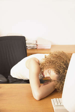 quell: Young businesswoman resting with her head down on a desk LANG_EVOIMAGES