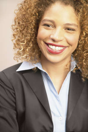 effrontery: Young businesswoman looking at camera smiling LANG_EVOIMAGES