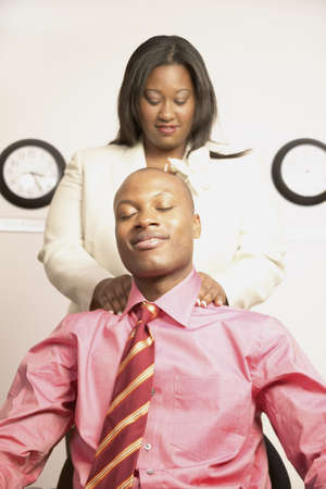soulful eyes: Young businesswoman massaging a young businessmans shoulder LANG_EVOIMAGES