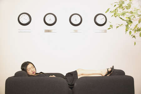 wasting away: Young businesswoman sleeping on an office couch