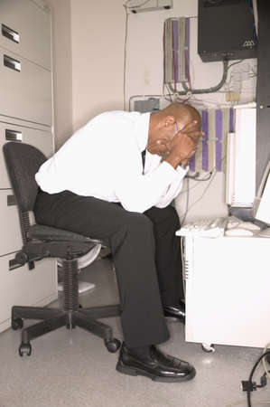 annoyance: Businessman sitting at a desk resting his head on his hands