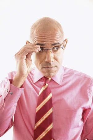 skepticism: Portrait of a businessman adjusting his eye glasses