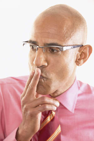 skepticism: Portrait of a businessman with two fingers on his lips