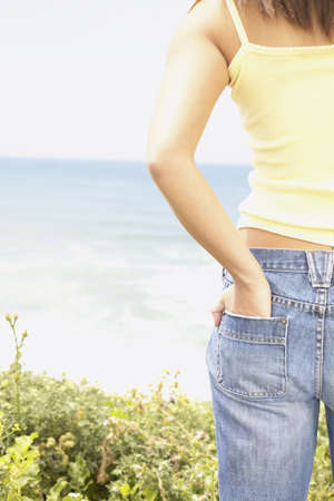 freewill: Rear view of a young woman at beach with her hand in her back pocket