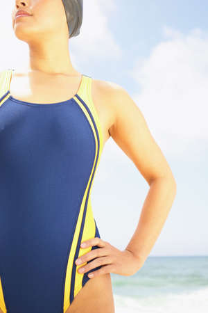 hauteur: Torso of a young woman standing at the beach in a swimsuit