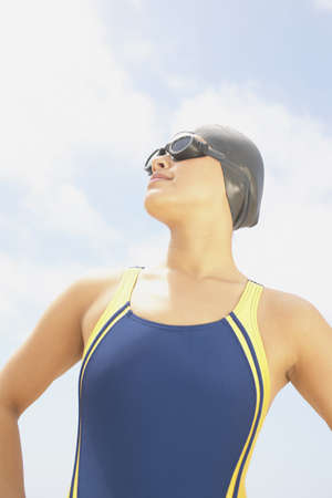 hauteur: Low angle view of a young woman standing on the beach wearing swimming gear LANG_EVOIMAGES