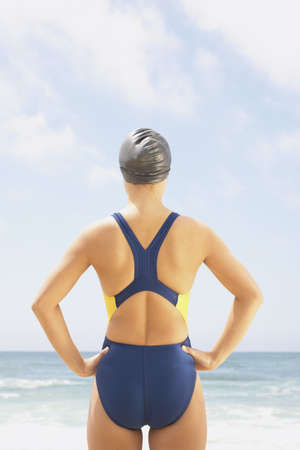 hauteur: Rear view of a young woman standing at the beach wearing a swimsuit with her hands open her hips