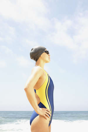 hauteur: Side profile of a young woman standing at the beach wearing a swimsuit