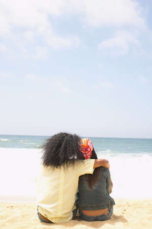 seres vivos: Vista trasera de una pareja de jóvenes sentados en la playa LANG_EVOIMAGES