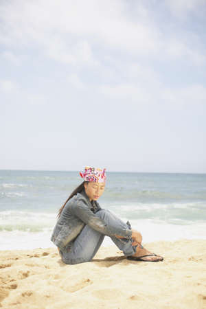 oceanic: Side profile of a young woman sitting on the beach