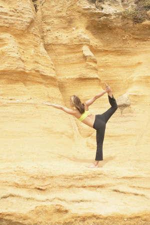 determines: Giovane donna in piedi su una roccia praticare lo yoga
