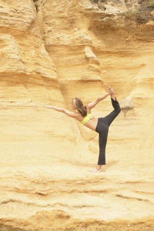 finesse: Young woman standing on a rock practicing yoga