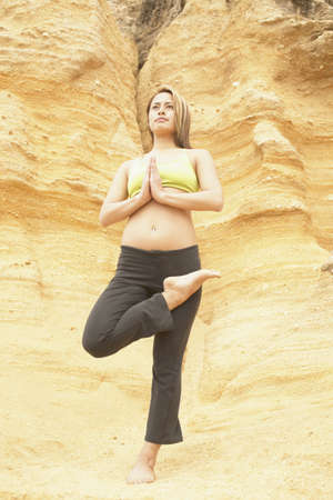 theology: Young woman standing on a rock doing yoga