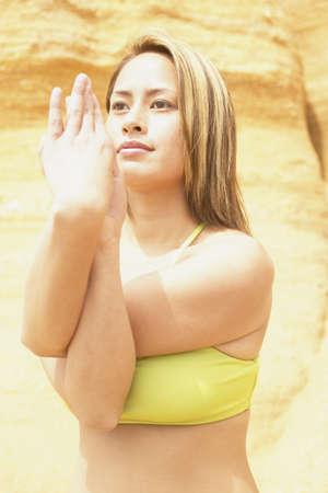 determines: Giovane donna in piedi su una roccia di eseguire esercizi di stretching