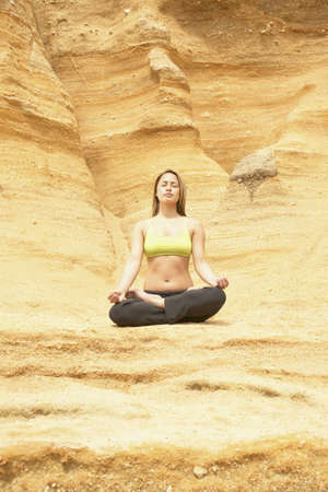 leeway: Young woman sitting on a rock meditating LANG_EVOIMAGES