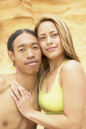 anecdote: Young couple standing on a rock holding each other