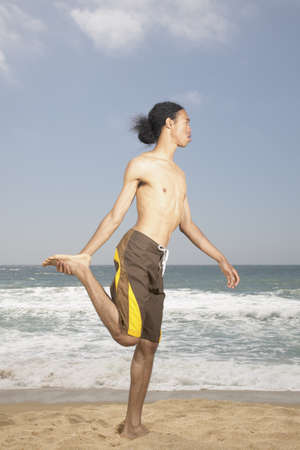 surrounds: Young man doing exercises on the beach LANG_EVOIMAGES