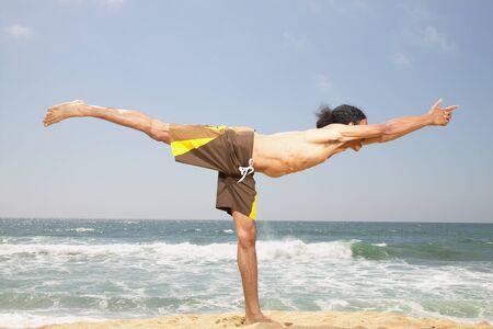 determines: Giovane uomo facendo esercizi di stretching sulla spiaggia